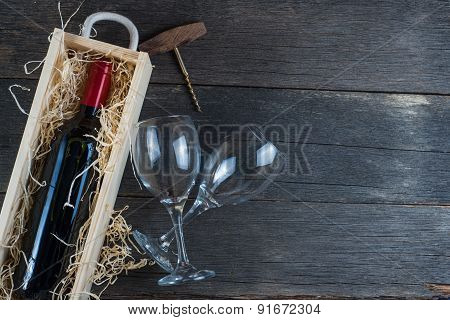Bottle Of Red Wine In Case And Glass On Rustic Wood
