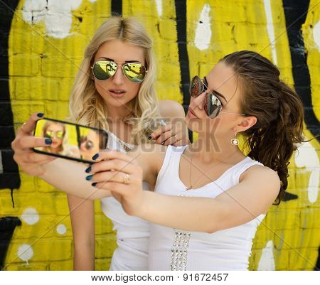 Happy attractive girls with smart phone take selfie against urban grunge graffiti wall.
