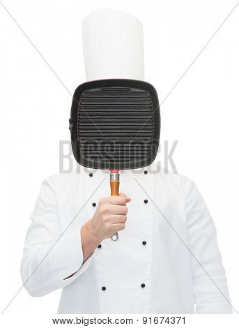cooking, profession and people concept - male chef cook covering face or hiding behind grill pan