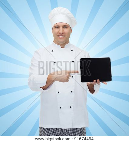 cooking, profession and people concept - happy male chef cook showing tablet pc computer black blank screen over blue burst rays background