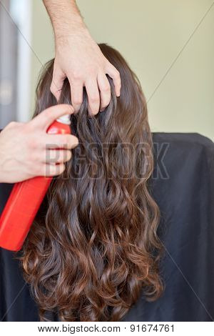 beauty, hairstyle and people concept - closeup of woman head and stylist hands with hair spray making hairdo at salon