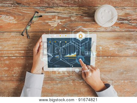 business, people, economics, statistics and technology concept - close up of hands pointing finger to tablet pc computer screen with virtual graph projection coffee cup and eyeglasses on table
