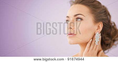 people, beauty, jewelry and accessories concept - beautiful woman with diamond earrings over violet background