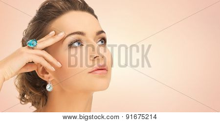 beauty, jewelry, people and accessories concept - close up of woman face with cocktail ring on hand and earrings over beige background