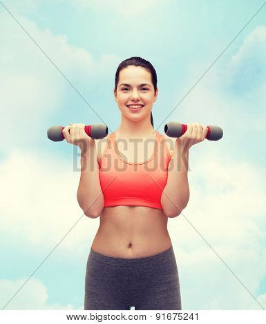 sport, exercising and healthcare concept - young sporty woman with light dumbbells