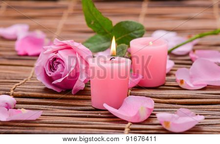 Candles and rose with Petals on mat