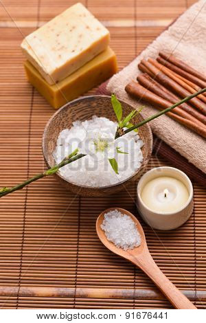 Beautiful spa setting with flower on bamboo mat close up