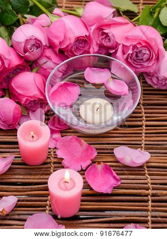 Three white Candles and rose with Petals on mat