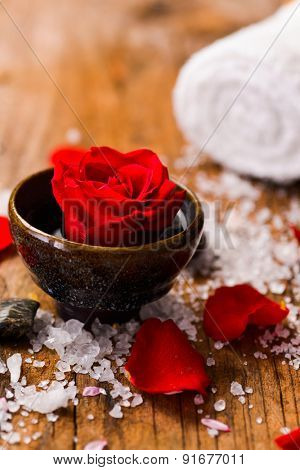 Red roses in bowl with petals in bowl with pile of salt ,stones on old wooden board