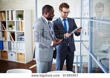 Two businessmen looking at data in touchpad at meeting