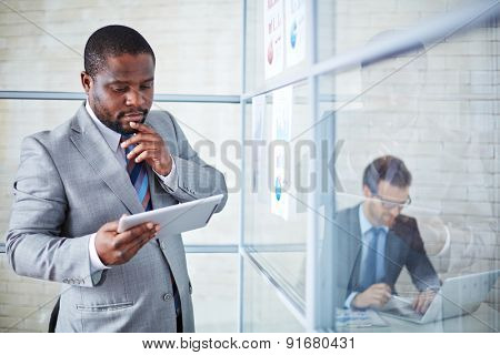 Pensive businessman with touchpad studying data for project