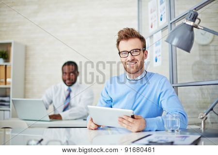 Young man with touchpad looking at camera during work in office