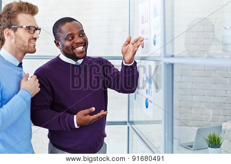 Male employee comparing financial data on papers and explaining it to colleague