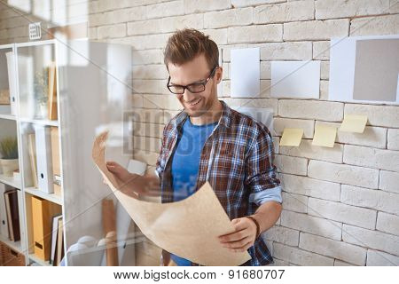 Young architect in casualwear reading document by the wall