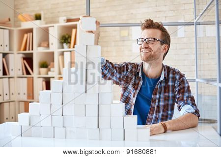 Happy architect in casualwear building paper pyramid in office
