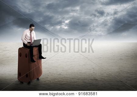 Man Sit On The Suitcase, Working With Laptop At The Desert.