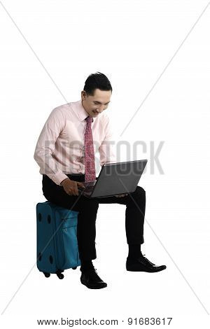 Man Working With Laptop Sitting On Suitcase