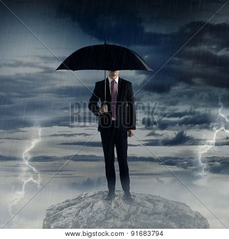 Man Holding Umbrella Standing On The Rock With Bad Weather
