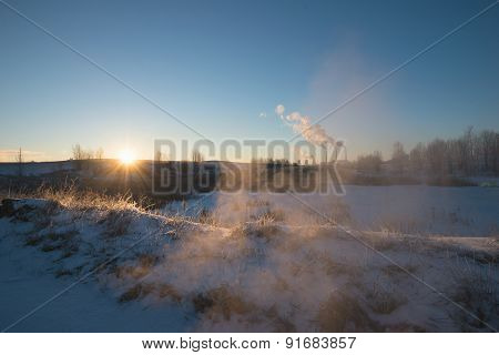 Winter Landscape With Factory Chimneys And Clouds Against The Sun