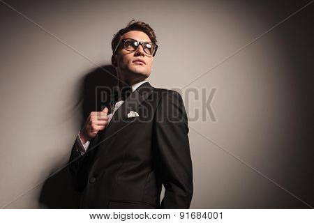 Handsome young elegant business man leaning on a wall while looking up.