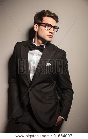 Side view of a elegant business man looking away while holding his hands in pockets.