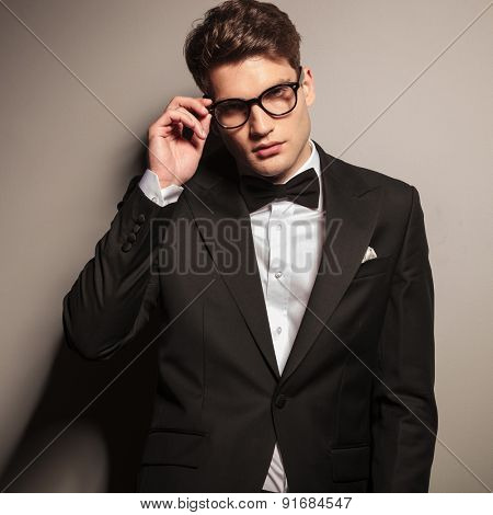 Attractive young business man fixing his glasses while looking at the camera.