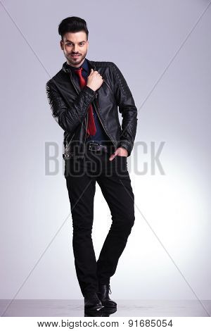 Smiling young business man standing on studio background with one hand in his pocket.