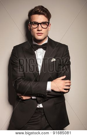Young handsome business man leaning on a wall while holding his hands crossed.
