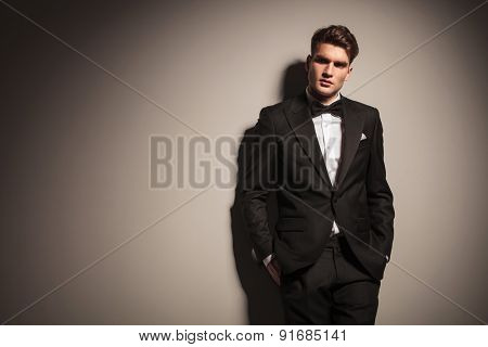 Elegant young business man leaning on a grey wall with his hands in pockets.