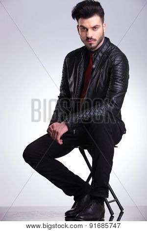 Side view of a young casual business man sitting on a chair on grey studio background.