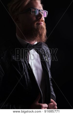 Portrait of a young business man looking up while pulling his jacket.