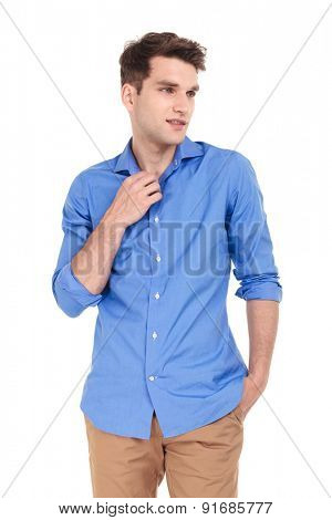 Attractive young man holding one hand in his pocket while fixing his shirt.