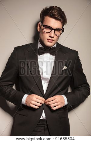 Young elegant business man closing his jacket while looking at the camera.