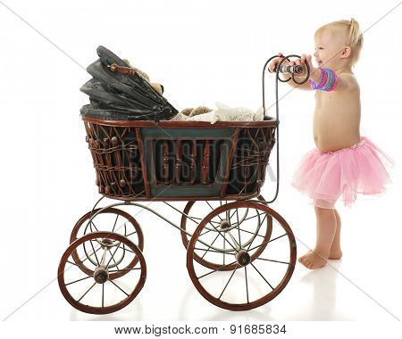 An adorable 2-year-old barefoot in a pink tutu happily taking her Teddy bear for a walk in an old buggy.  On a white background.
