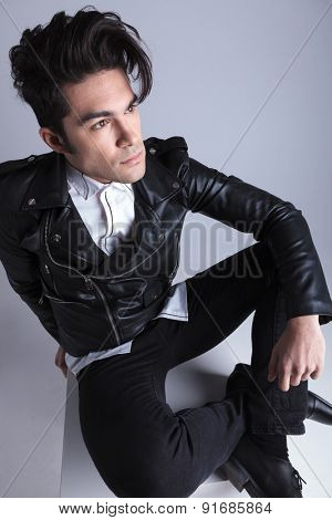 Angle view of a fashion man looking away from the camera while relaxing on studio background.