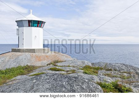 White small lighthouse, beacon on a cliff.
