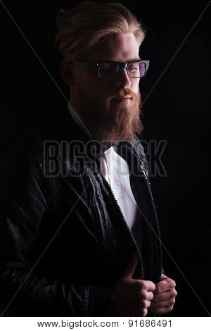 Long beard business man looking down while pulling his jacket.