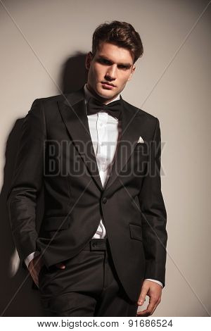 Attractive young business man holding one hand in his pocket while looking at the camera.