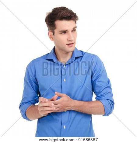 Worried young man holding his hands together while looking to his side.