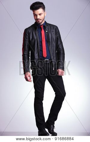 Handsome young business man standing on grey studio background looking down, full body picture.
