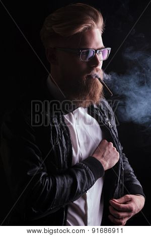 Portrait of a young business man searching in his inside pocket while smoking a cigarette.