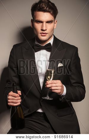Portrait of a young elegant business man holding a glass and a bottle of champagne while sitting.