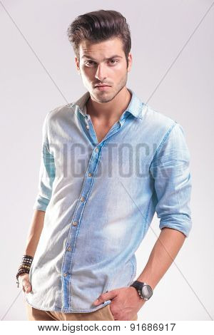 Portrait of a casual young fashion man posing with his hands in pockets.