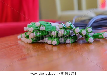 A group head connector fiber optic green color on brown table.Fiber Optics connectors. Internet Serv