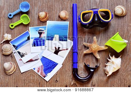 high-angle shot of rustic wooden table full of summer stuff, such as different conches, seashells and starfish, a diving mask and a snorkel, beach toys and some photos, shot by myself, of beach scenes