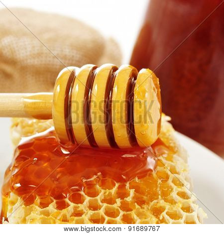 closeup of a honeycomb and a honey dipper with honey, and some honey jars in the background