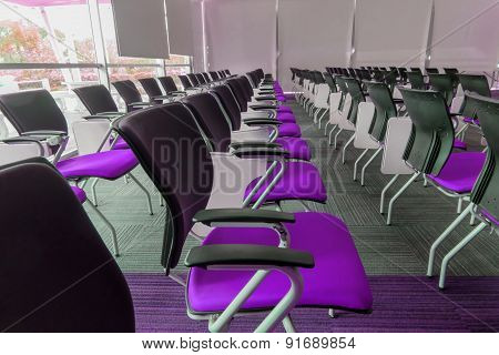 Many purple chairs arranged neatly in a training room.