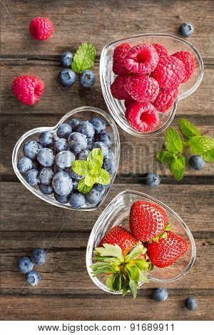 Mix Of Fresh Berries In A Glass Ramekins In Shape Of Heart, On Wooden Background, Top View