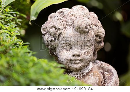 Old Statue Of An Infant Angel Or Cupid In The Garden