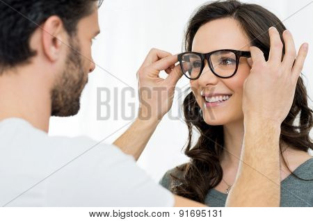 Optician putting a new pair of eyeglasses on a patient
